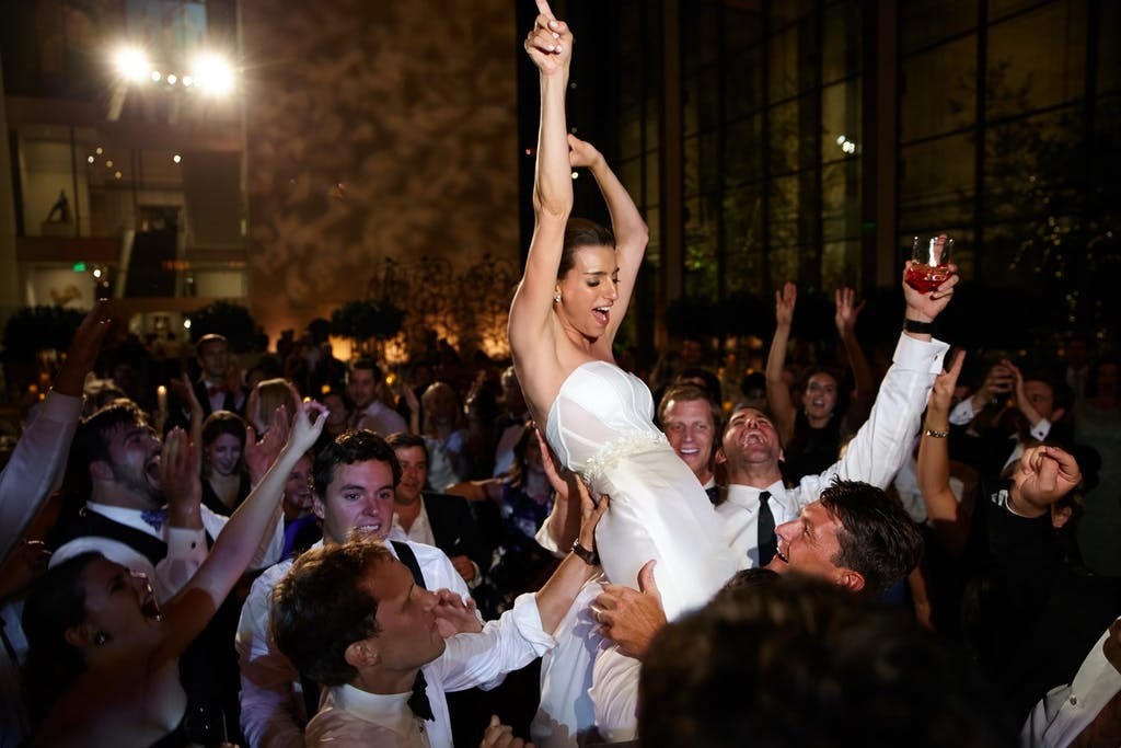 A bride is being lifted by the groomsmen, she has her hands in the air and the crows is laughing and smiling.