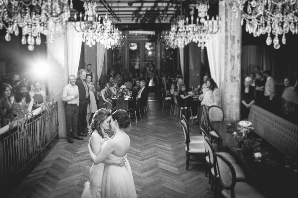 Two brides are on the dance floor with chandeliers above. Wedding guests surround the area and watch the couple.