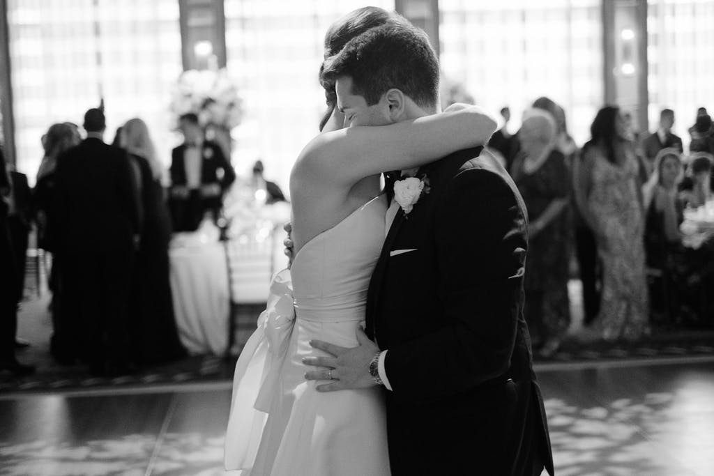 A bride and groom hug on the dance floor. Wedding guests surrounding them.