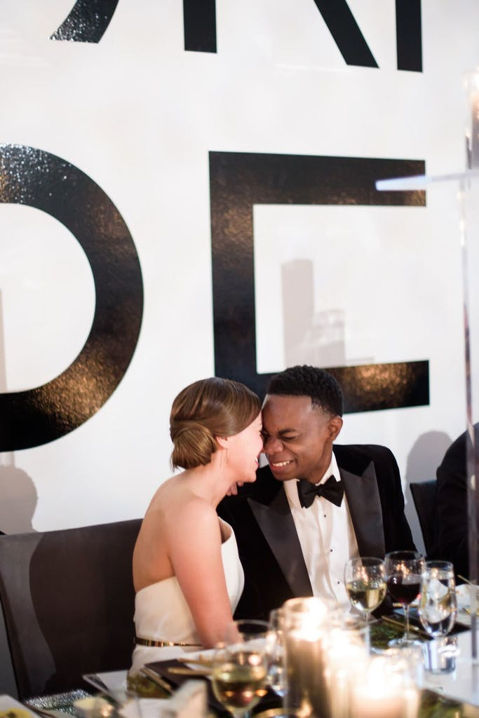 A bride and groom sit at their table at the reception. They are leaning into each other touching faces.