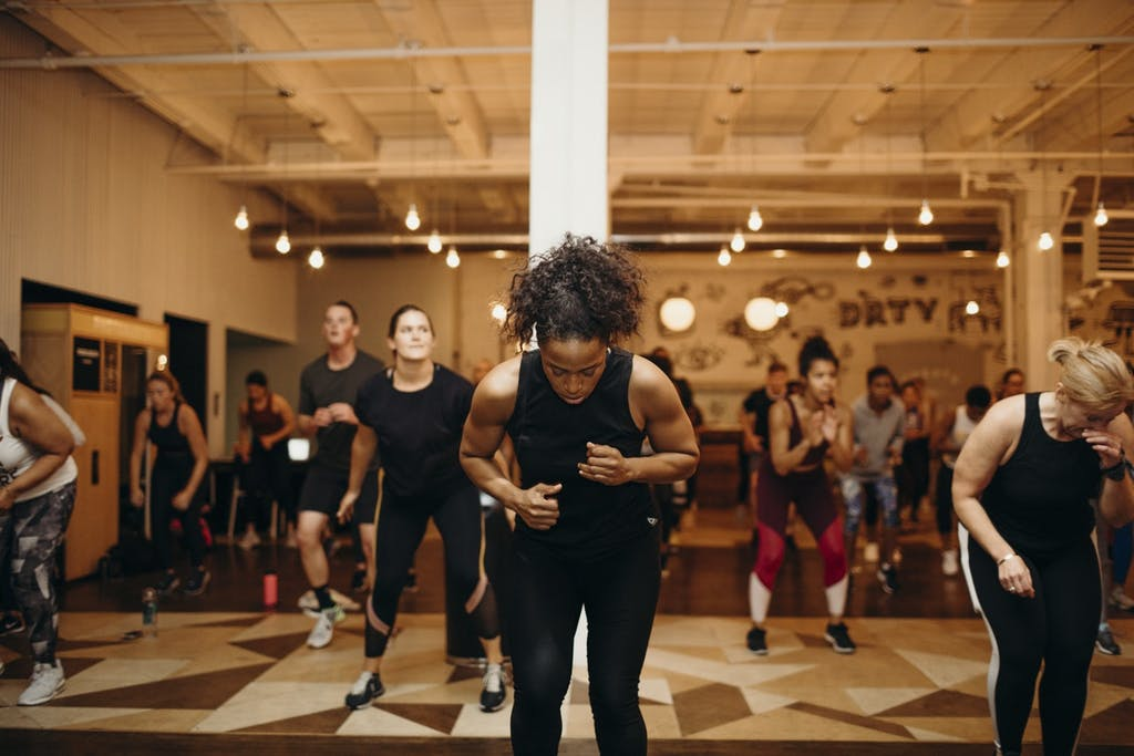 a work out instructor leads a class of people working out.