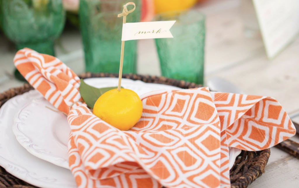 orange printed napkin topped by a lemon and seating name tag