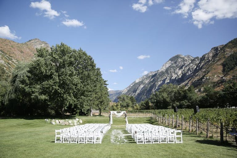 White chairs and altar in the midst of a large field with mountains and a large tree in the background
