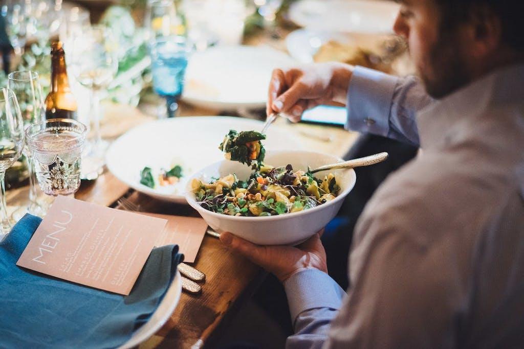 Man serving himself all-vegan salad with chickpeas.