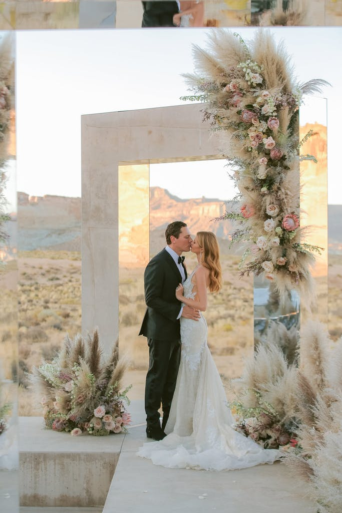 bride and groom kiss under rectangular, mirrored archway with desert backdrop