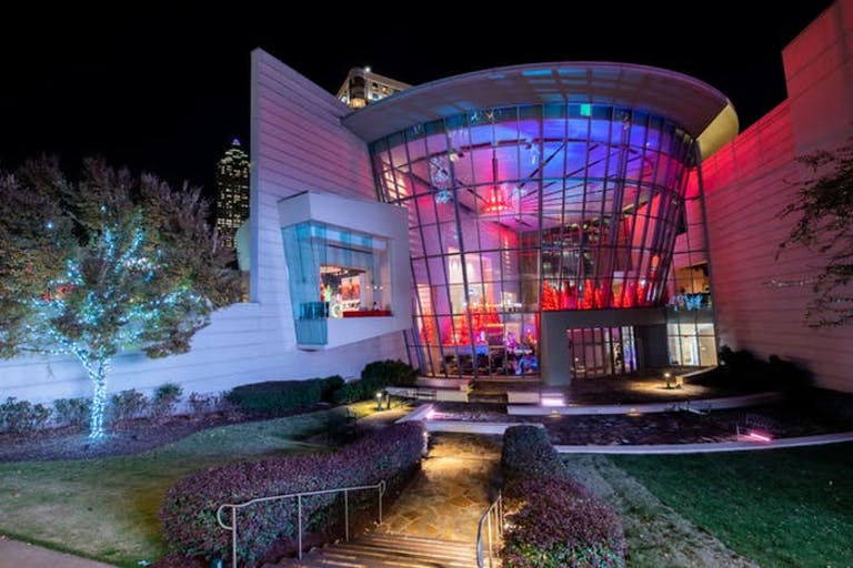 The outside of a building with large glass windows looking into a room of red and blue lights.