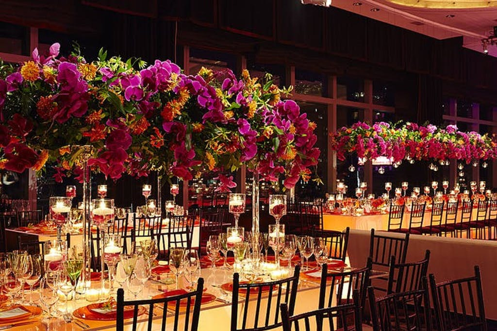 red orchids and bright orange flowers hover over lit tabletops at wedding