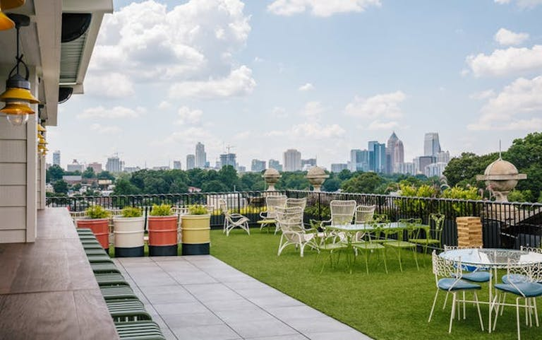 Outdoor lawn with tables and chairs and a beautiful view of the Atlanta skyline.