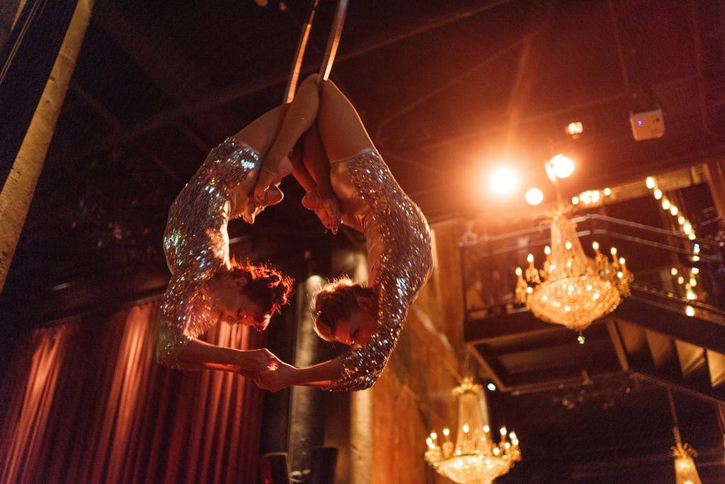 Two aerialists in sequin leotards hand suspended in the air while holding hands