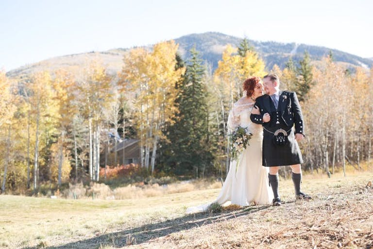 Bride and groom in field with forest and mountain in the background