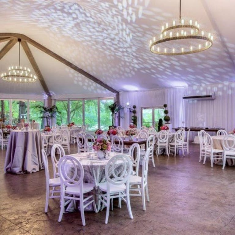 White room with low roof and candle chandeliers handing down over white tables and chairs