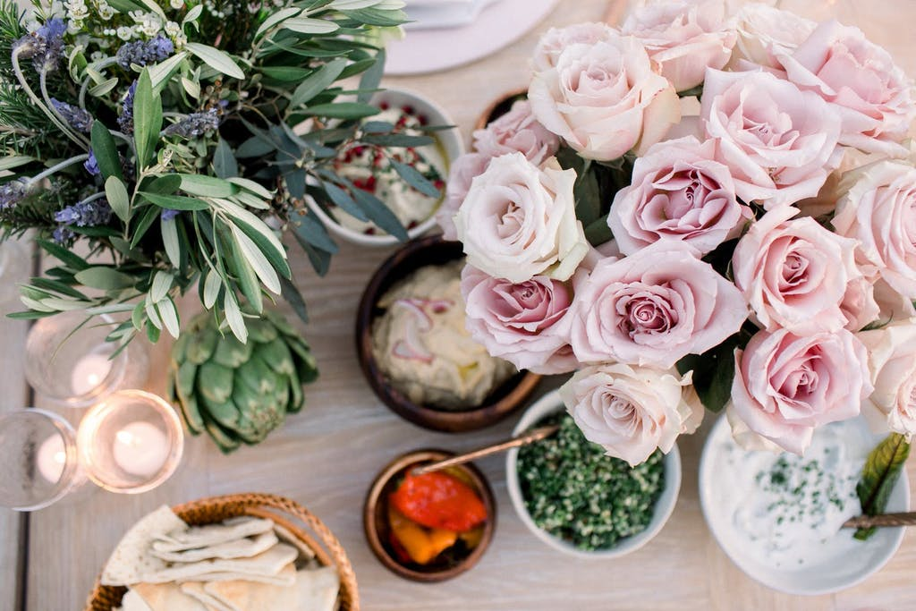 still life photograph of blush-colored roses, sage, artichoke, votive candles, and bowls of pita and various spreads