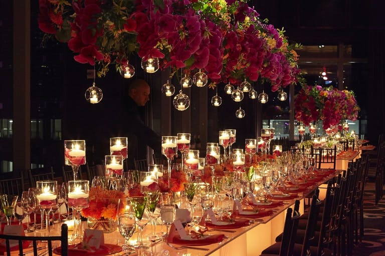 Table with candles in red wax throughout and rad roses hanging above