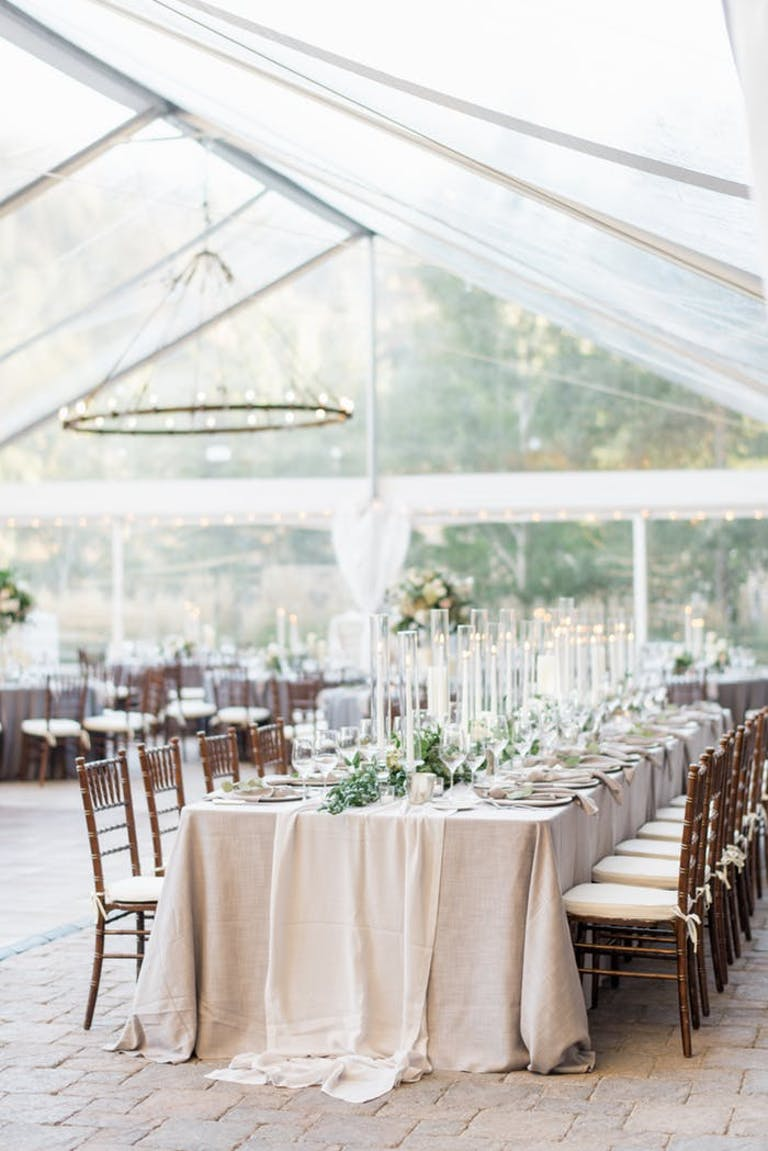 White tent with table and pink tablecloth.