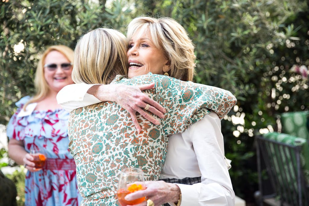 two women hug as they greet each other at an outdoor dinner party