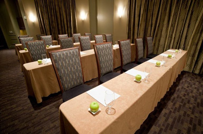 Tan table with white napkins and green apples at each place.