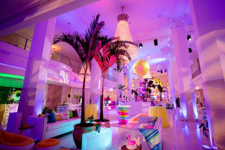 Room with purple hue and white pillars and mini palm trees