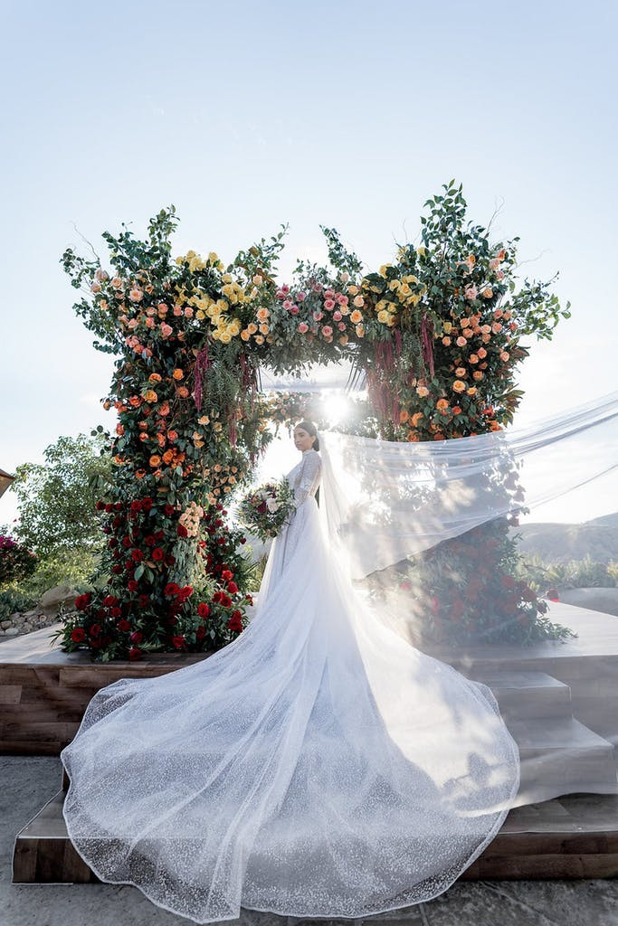 bride with windswept veil stands in front of a bloom-covered ceremonial arch and setting sun