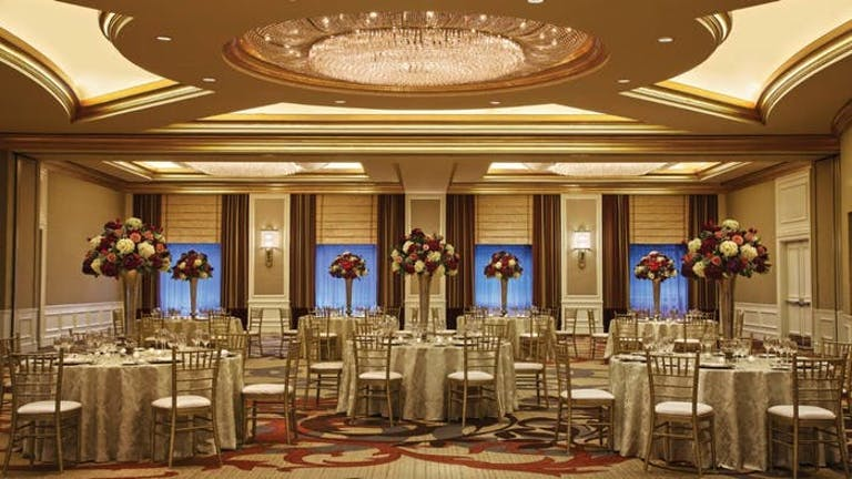 Large room with fancy tables with red and white flower centerpieces