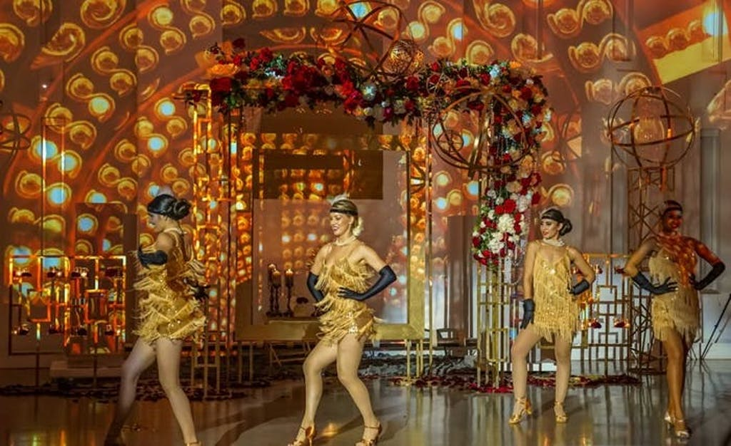 golden dancers in fringed dresses entertain at gatsby themed celebration