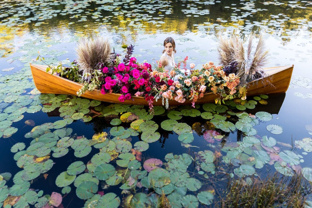 Woman sitting in a flower-filled canoe in a lily pond