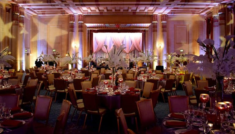 Large room with red tint and chairs and tables all around with curtains and stage at the end