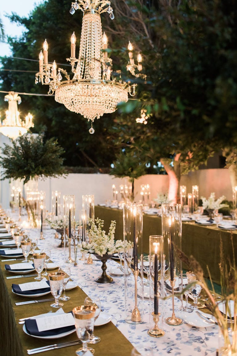 Large black candles with large white chandelier hanging down.