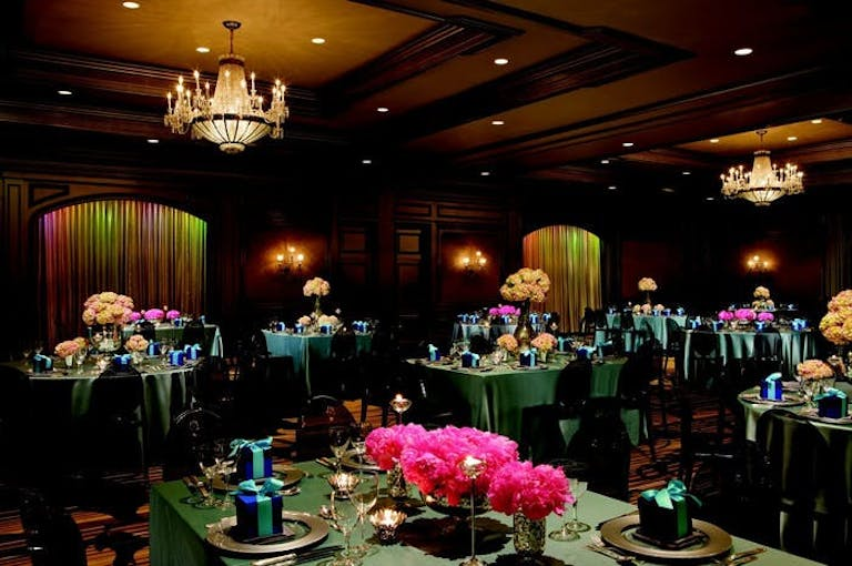 Dark room with green tables with pink flowers centerpieces