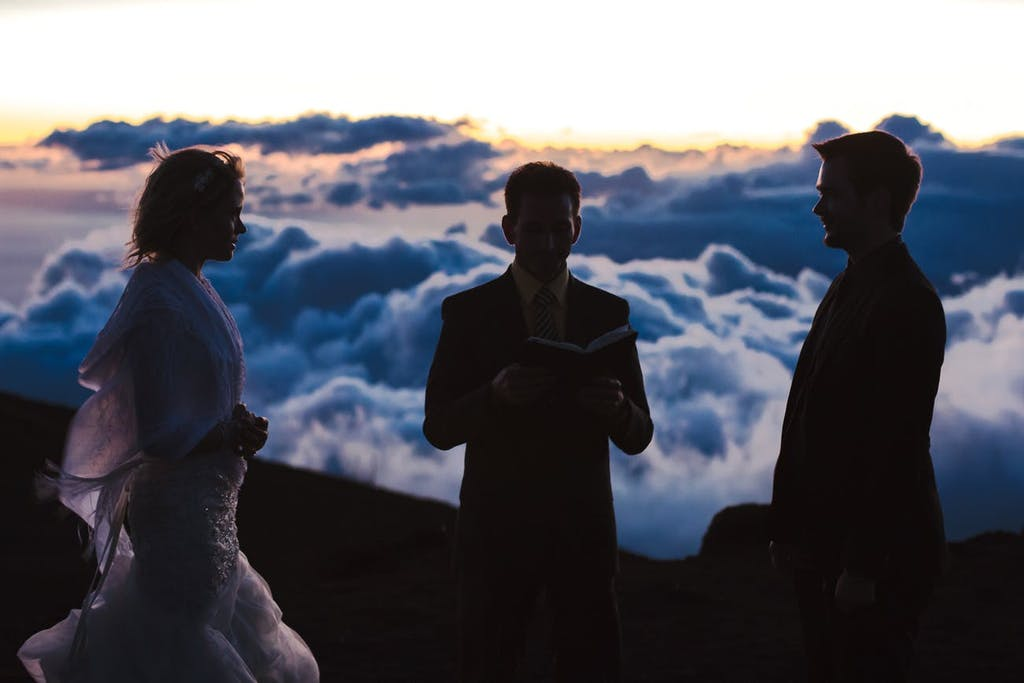 Officiant married bride and groom on mountain above the clouds.