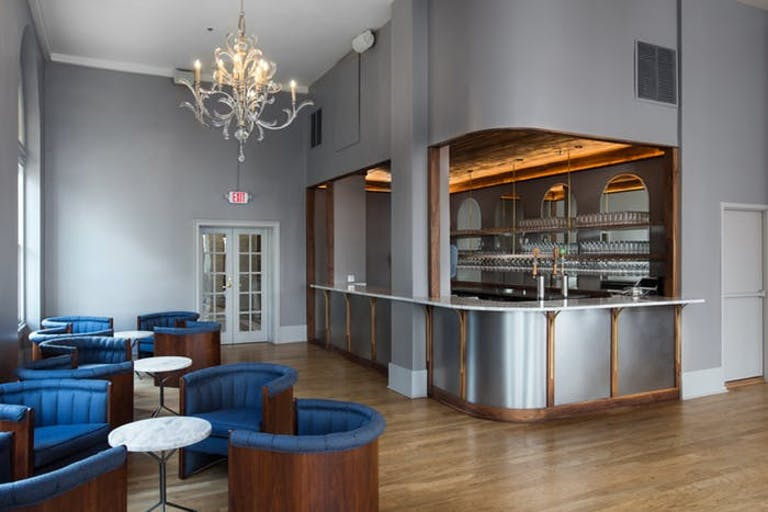 Modern bar with silver around and small tables with circular blue chairs