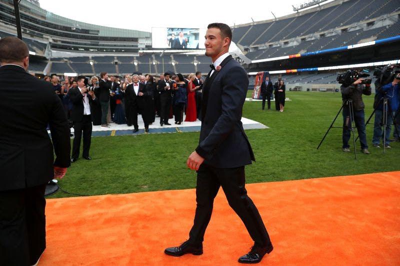Man in tux walks on orange carpet in Soldier Field.