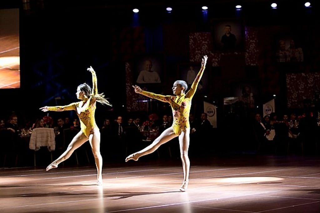 Two young girls in yellow leotards perform on stage with audience behind them.