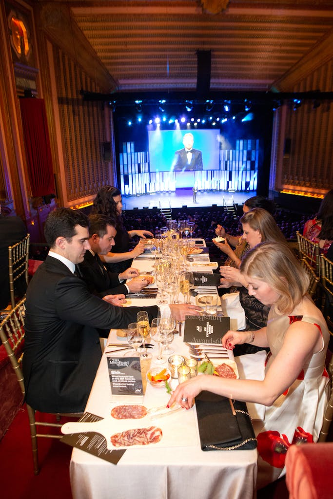 Guests enjoy sit-down dinner with stage and giant screen in background.