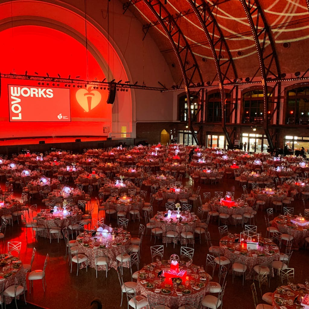 Large ballroom with banquet tables and red uplighting.