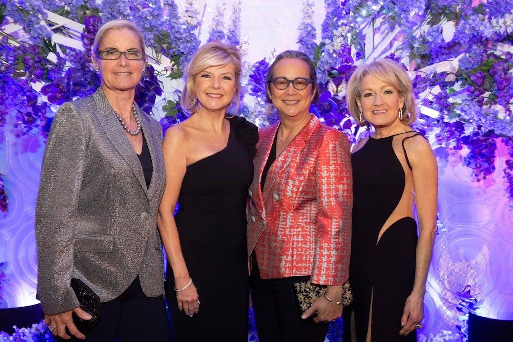 Four women pose in front of shimmering, violet-floral backdrop.