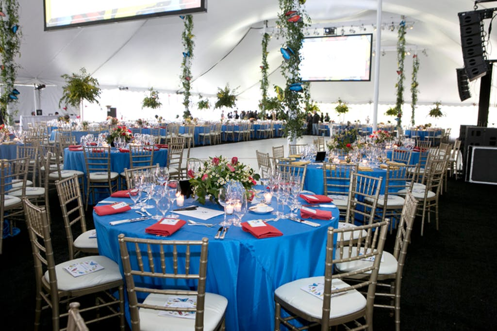 Tented reception room with banquet tables covered in blue linens and red napkins.