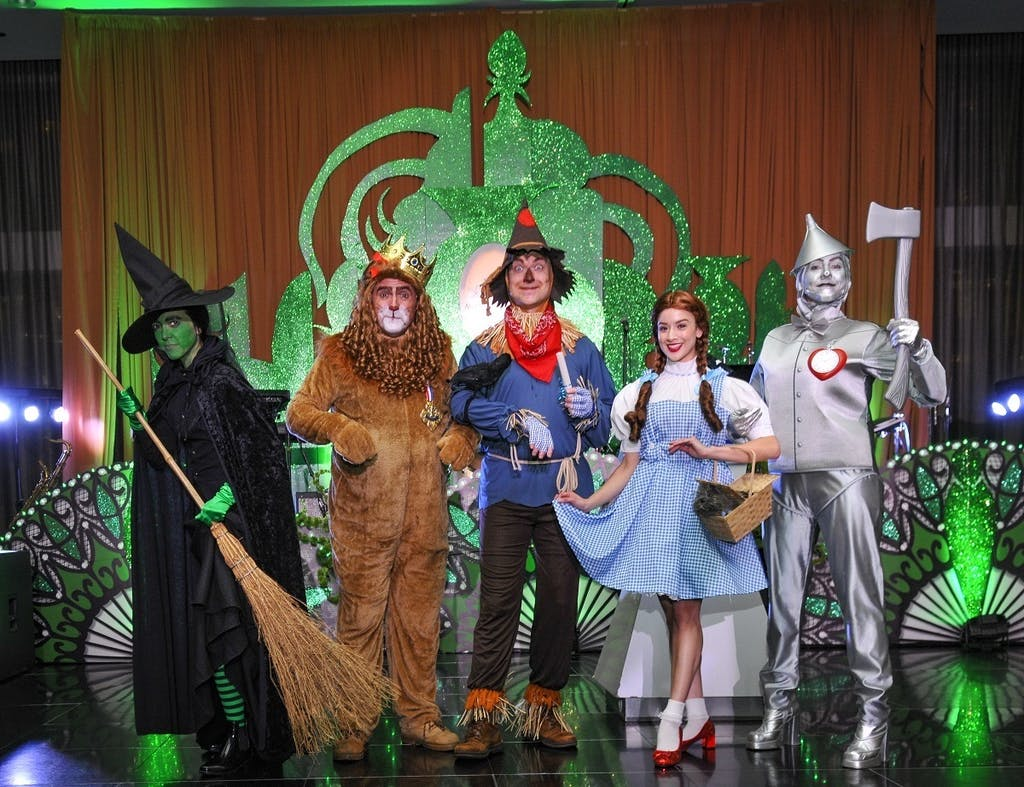 People pose as Wicked Witch of the West, the Cowardly Lion, the Scarecrow, Dorothy, and the Tinman in front of an Emerald City cutout.