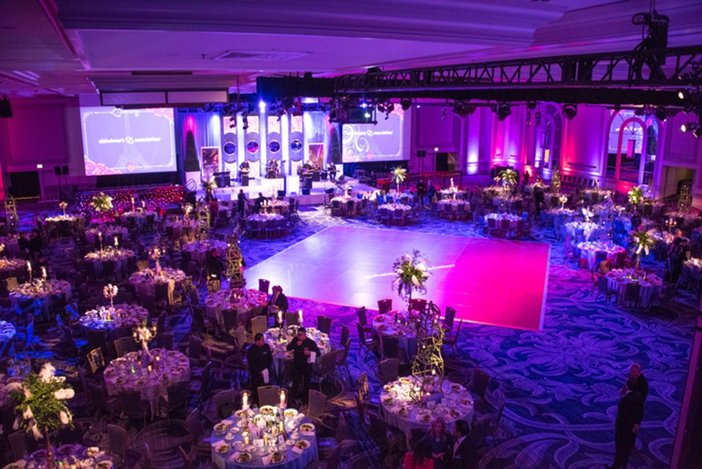 Industrial ballroom with banquet tables, dance floor, and pink/purple uplighting.