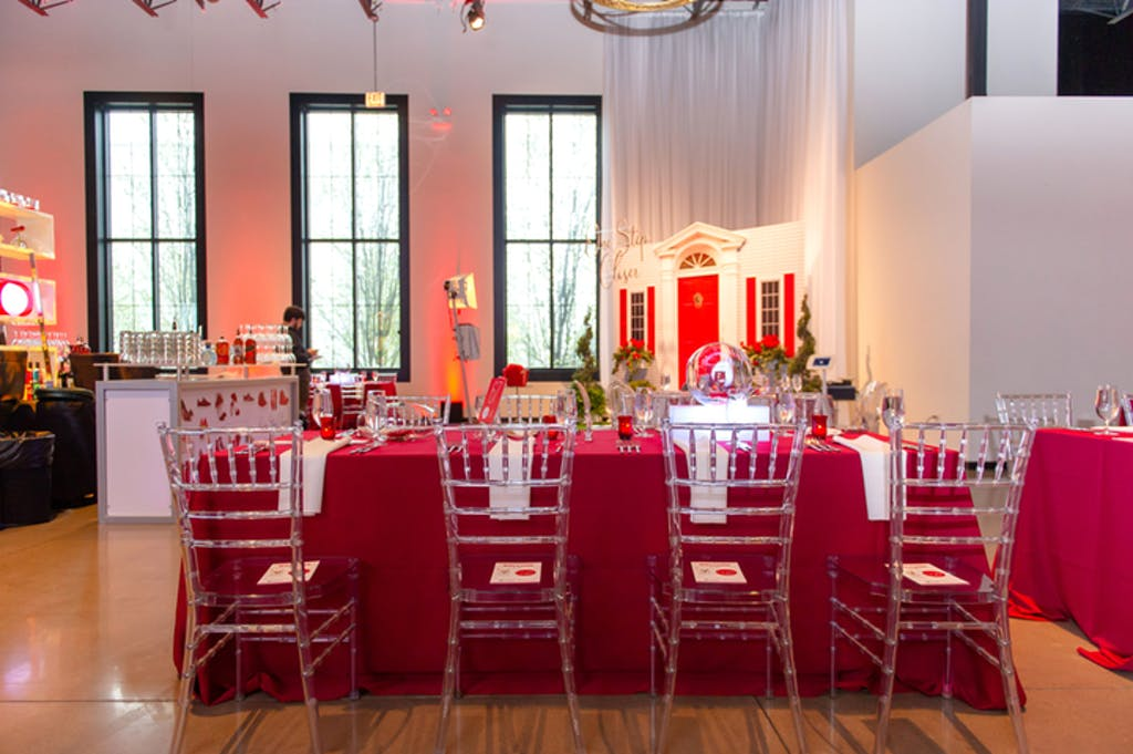 Banquet room featuring table covered in red linens with lucite Chiavari chairs.