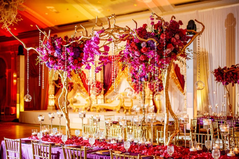 A gold and yellow background and a pink floral centerpice that extends very tall with gold antler-like accents and gold stems. Gold beads hand from the arrangements