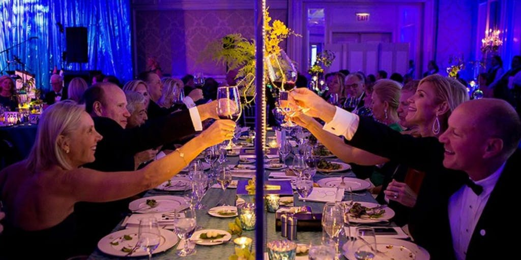 Guest cheers toward center of rectangular banquet table against backdrop of royal blue uplighting