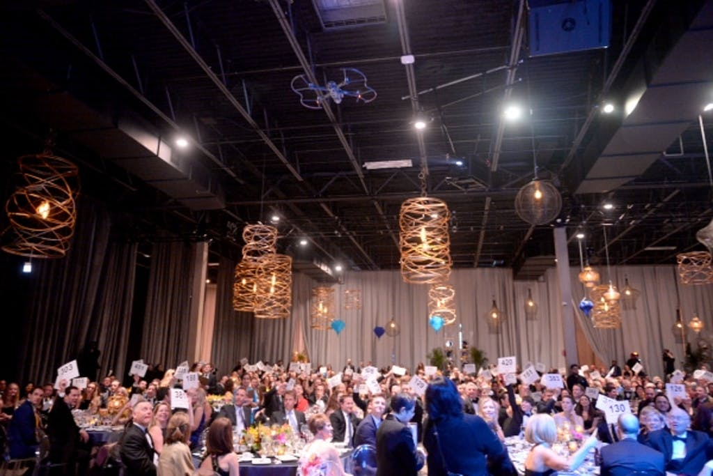 People at seated dinner reception with gold-spiral lighting suspended overhead.