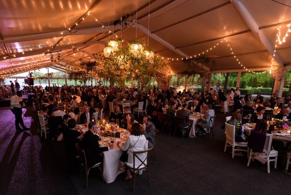 Tented ballroom with string lighting and guests sitting at banquet tables.