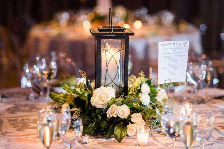 a single candle inside a black lantern with small leafy greens and white florals surrounding
