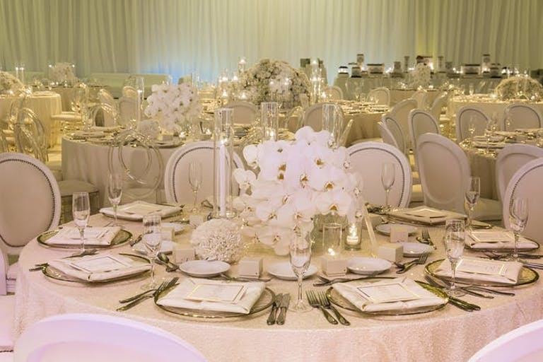 Many round tables in a event space with short orchid wedding centerpieces