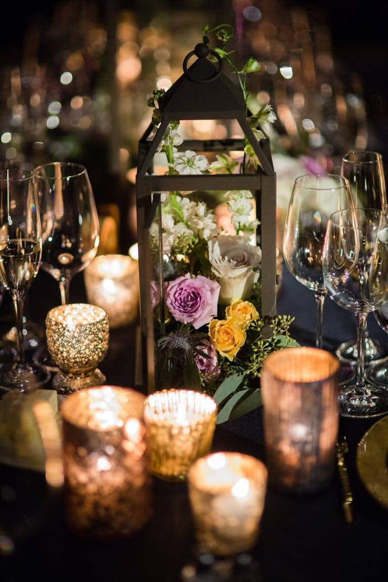 several gold flaked votive candles surrounding a lantern with purple and yellow florals inside
