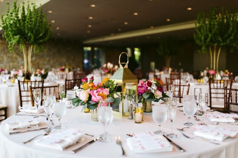 A round table with white linen and place settings. Multicolored florals surround a golden lantern with a candle inside.