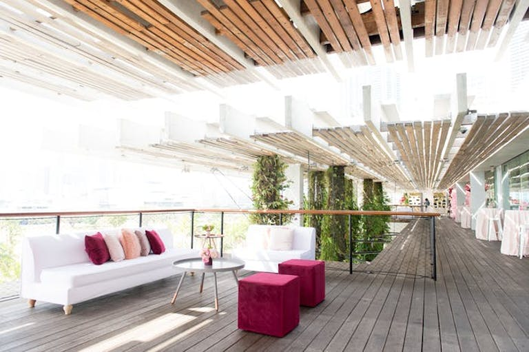 bamboo ceiling with luxe white furniture in an indoor/outdoor area.