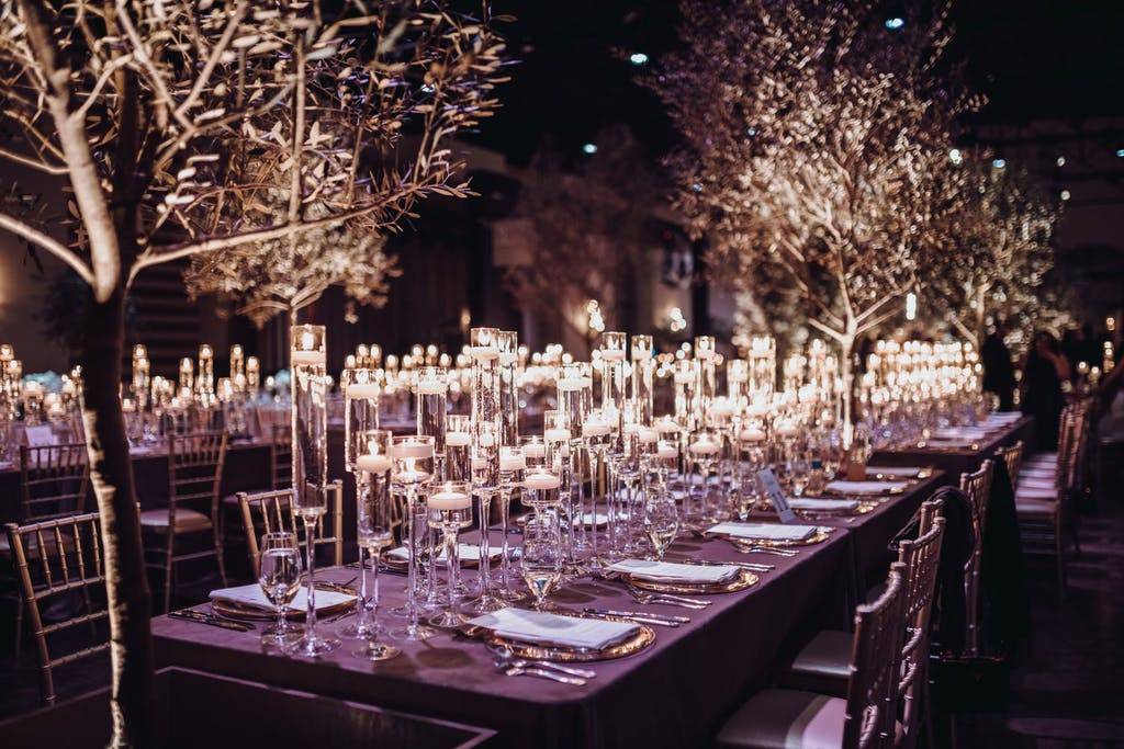 Banquet hall with two candlelit rectangular tables and winter tree foliage.