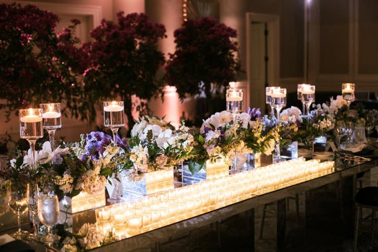 long table with many small orchid wedding centerpieces